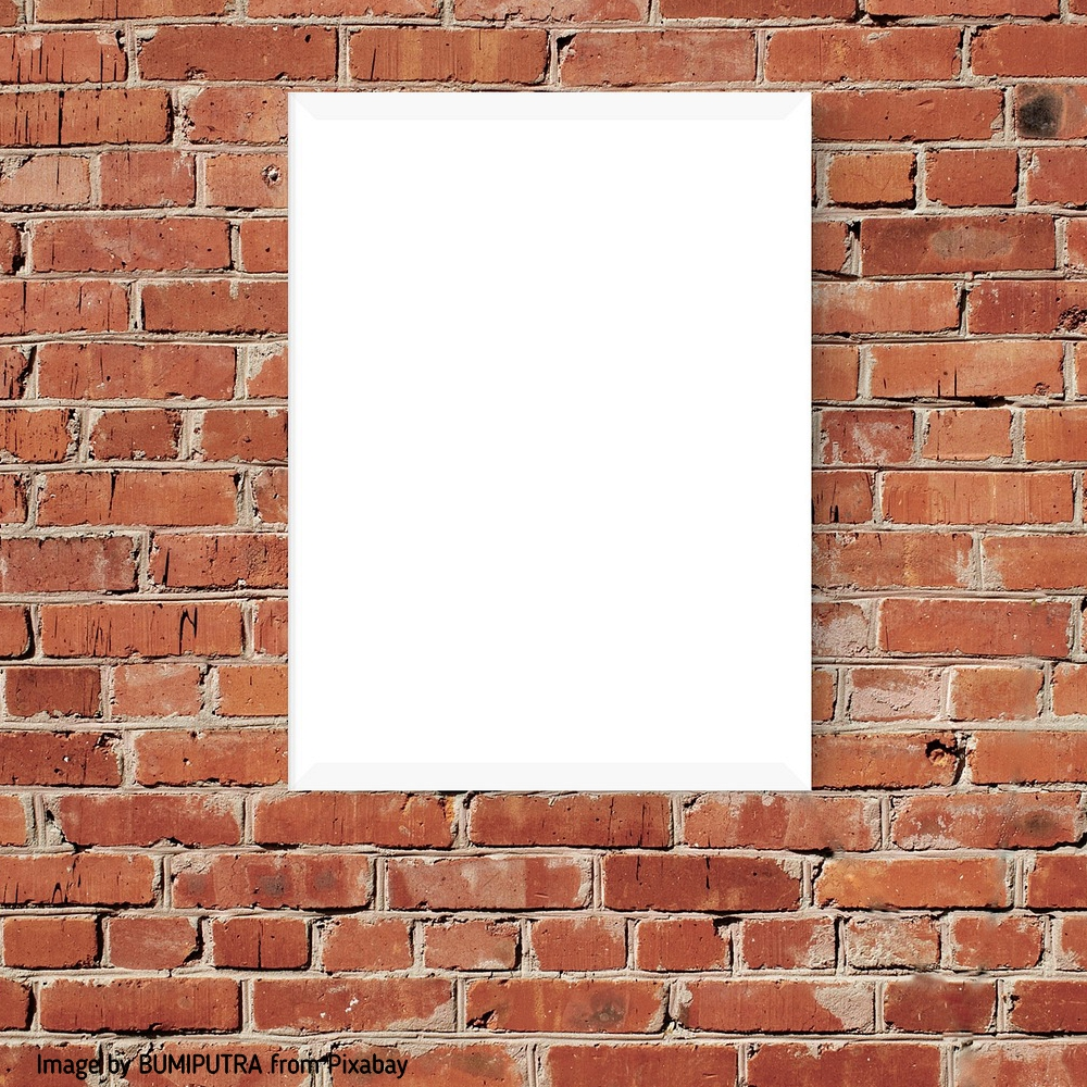 a blank canvas hung on a brick wall