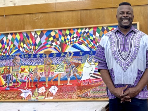 Ibiyinka Alao standing by a large piece of his art